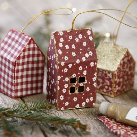 A card and fabric Christmas house decorated with glitter for hanging